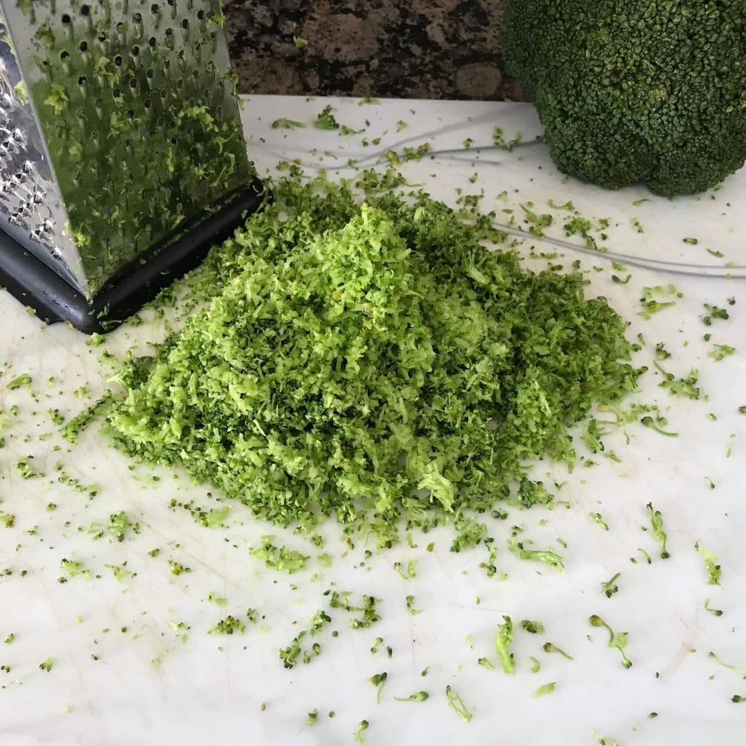Grated broccoli is on the cutting board