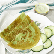A plate of cucumber dosas on the table along with chutney by the side