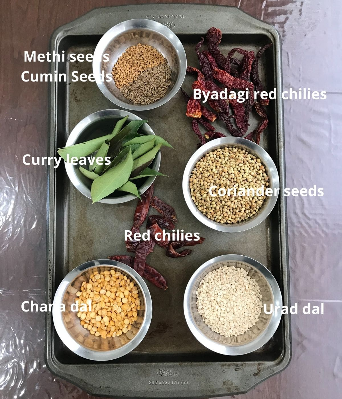 A tray is filled with sambar powder ingredients like red chilies, coriander seeds, and urad dal