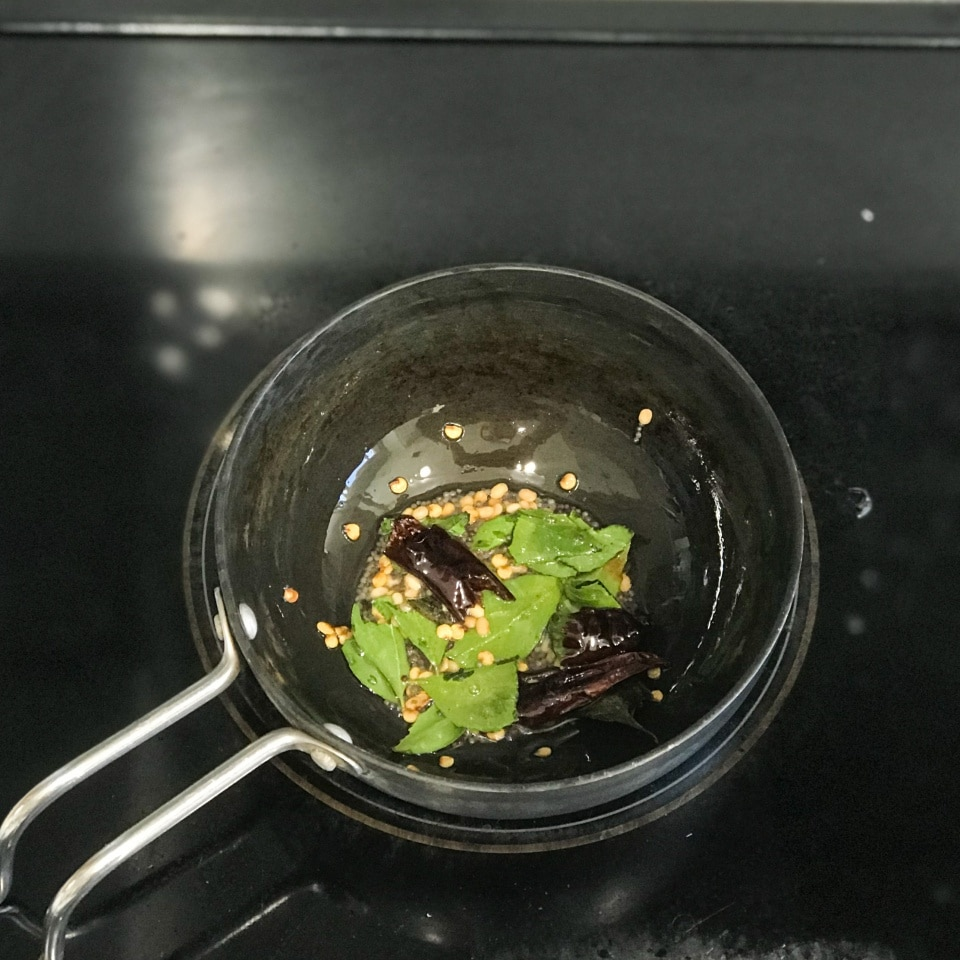 A small pan with oil and spices over the stove top