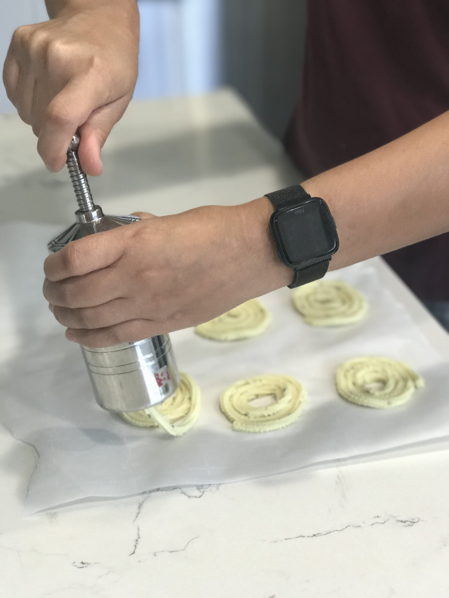 A lady is pressing the chakli dough into circular shape on the counter tops