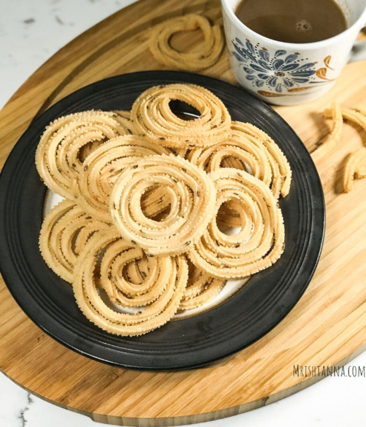 A plate full of chakli is on the table along with cup of coffee.