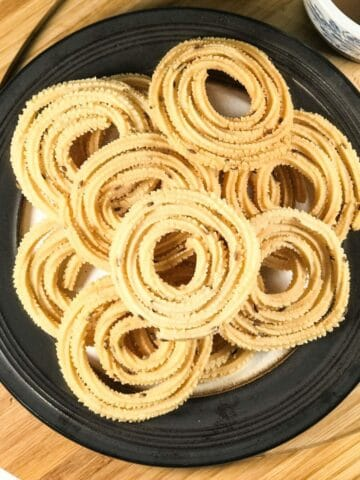 A plate is with chakli on the table
