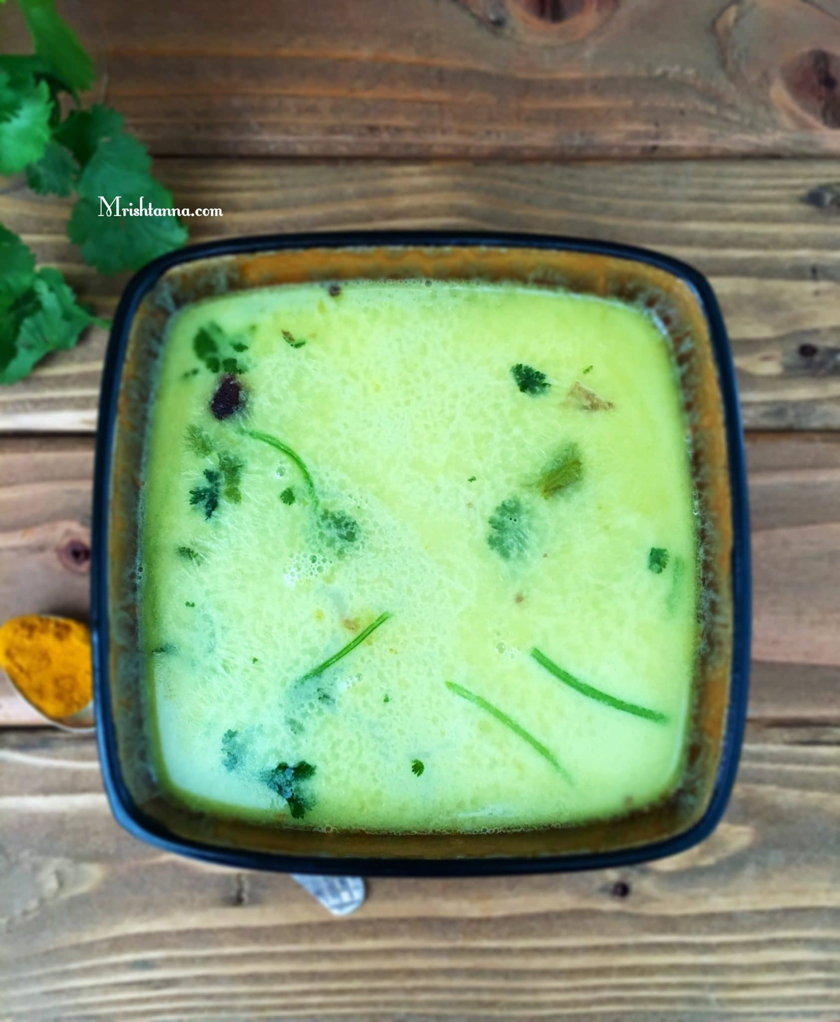 A bowl is filled with moong dal rasam and topped with cilantro
