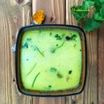 A bowl of moong dal rasam and topped with cilantro