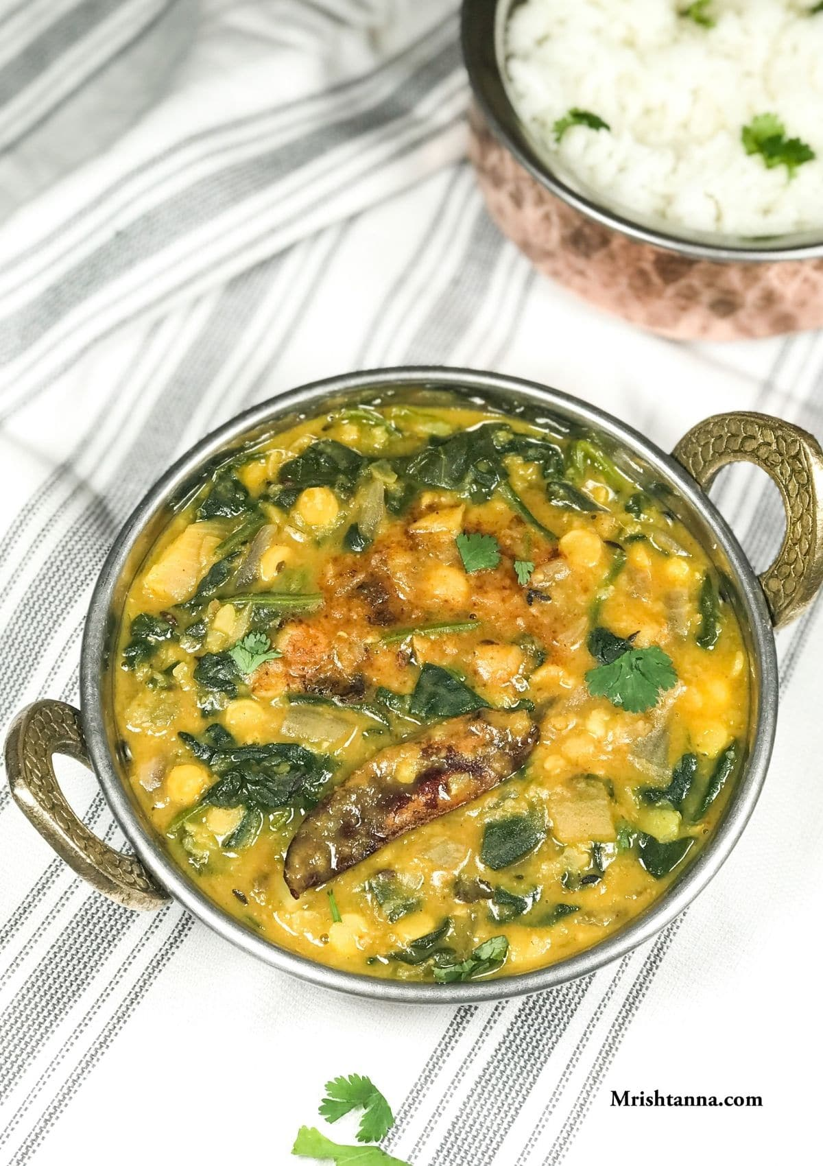 A bowl with spinach dal and garnished with red chili and cilantro