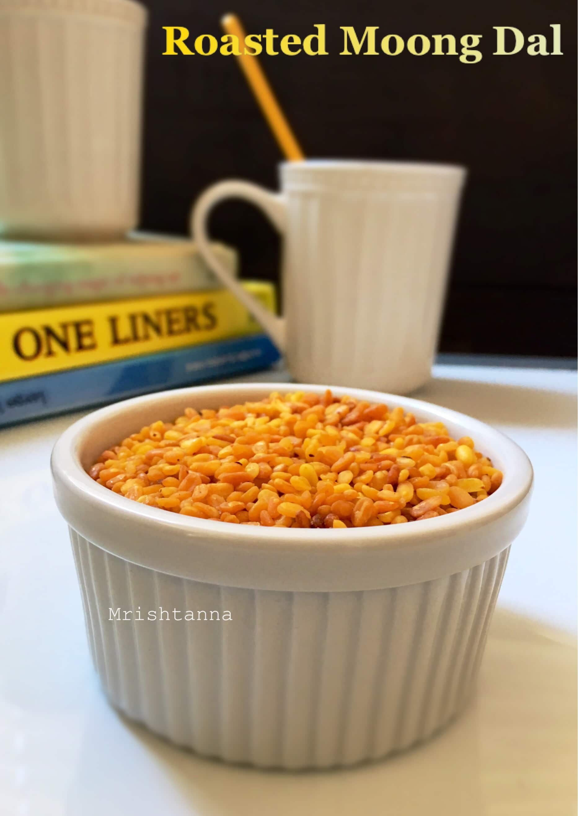 A cup of roasted yellow moong dal on the table along with cup of chai