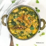 Spinach dal is in the copper bowl and tempering on the top