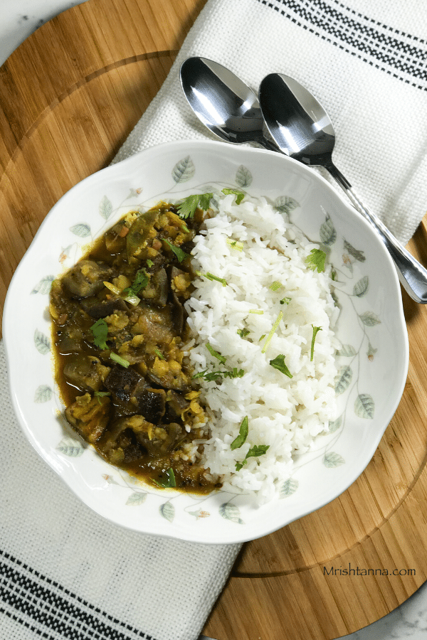 A plate with brinjal sambar and steamed rice is on the serving tray