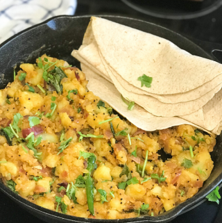 A pan filled with potato curry along with roti on the side.