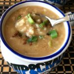 oatmeal soup is in the soup bowl and topped with green onions