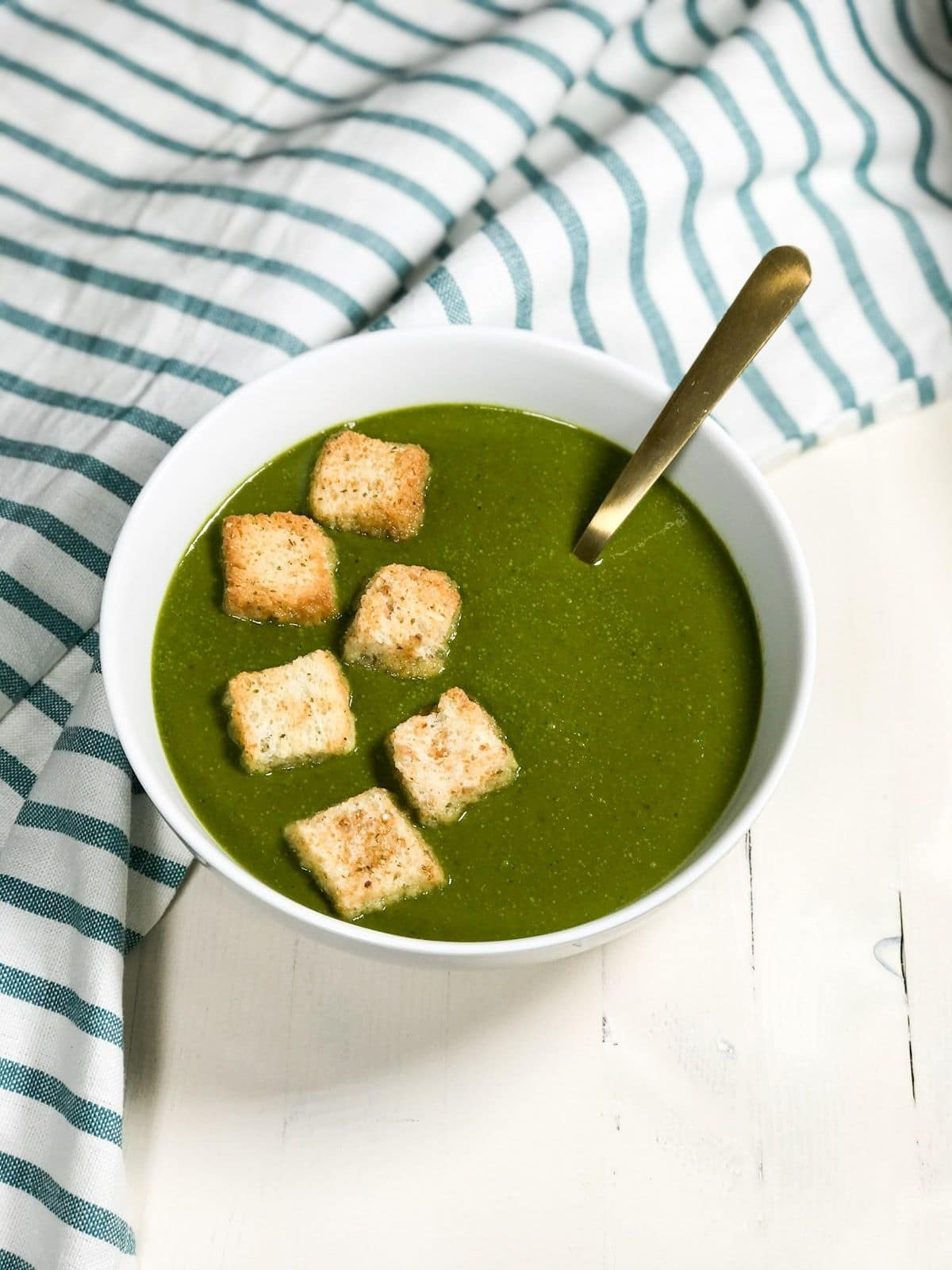 A bowl is filled with vegan spinach soup and a golden spoon is inserted