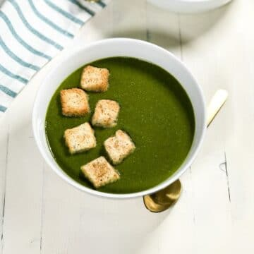 A white bowl of spinach soup is topped with croutons