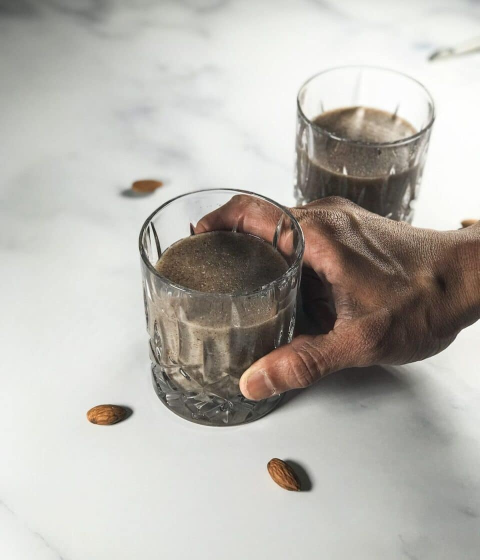 A man is holding the glass of ragi malt over the table