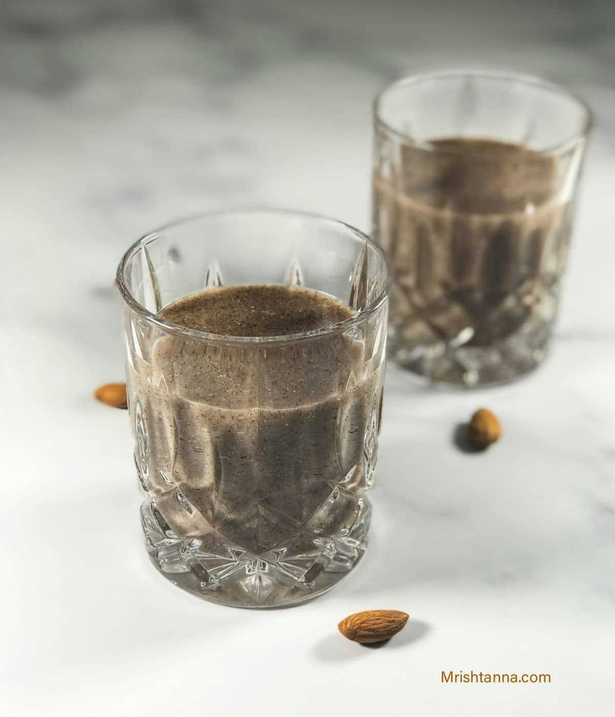 A glass is with ragi malt drink on the white board.