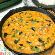 A pan of zucchini curry on a table and topped with cilantro