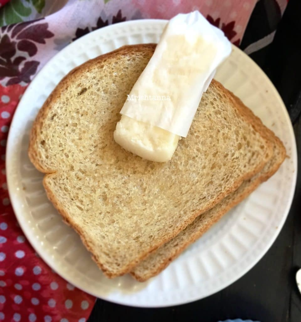 A sandwich cut in half on a plate, with Vegan Butter