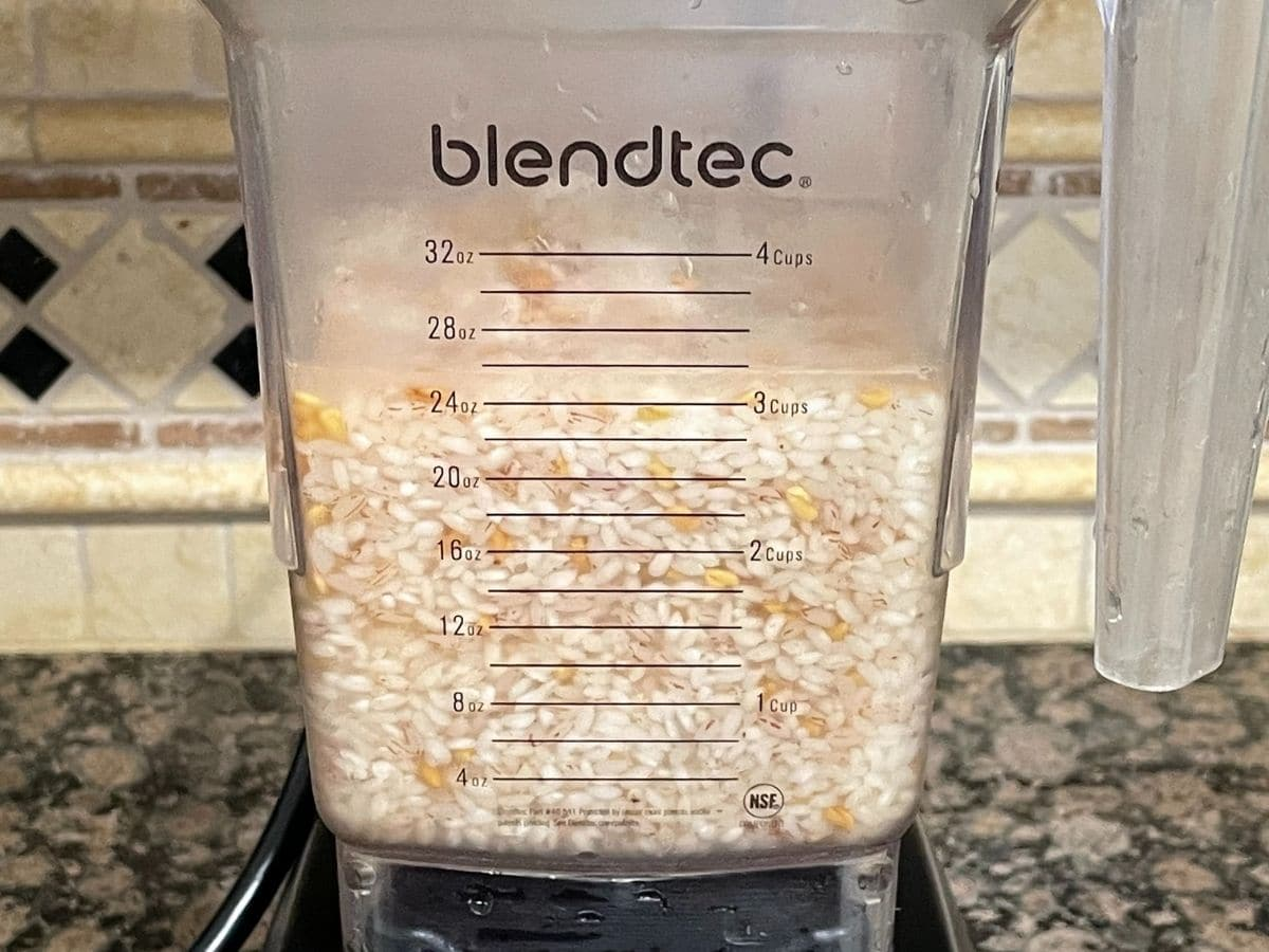A blender is filled with soaked rice and methi seeds and water