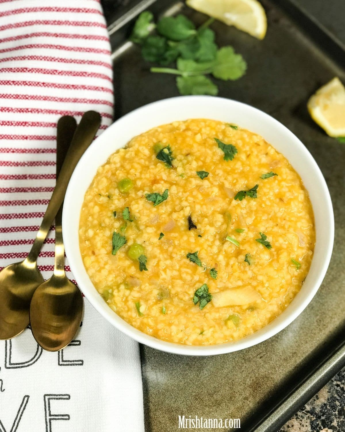 A white bowl with dalia khicdi and garnished with cilantro and lemon slices