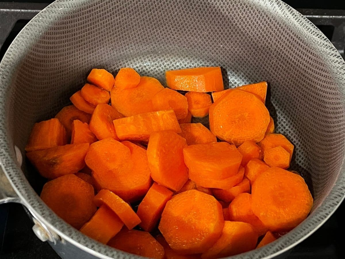 A pan is with chopped carrots over the heat