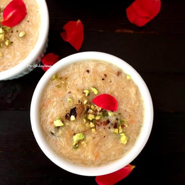 A bowl of sevai kheer and topped with pistachios and rose petals
