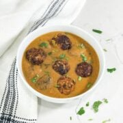 A bowl of curry with cabbage and kofta