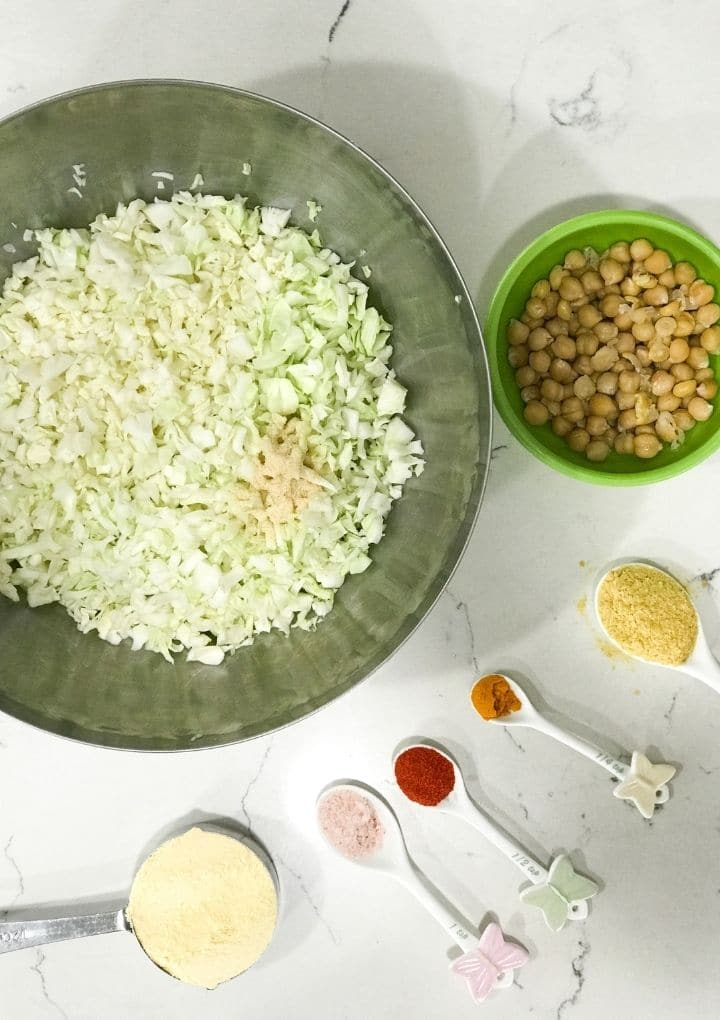 In a big bowl shredded cabbage and other ingredients for cabbage kofta