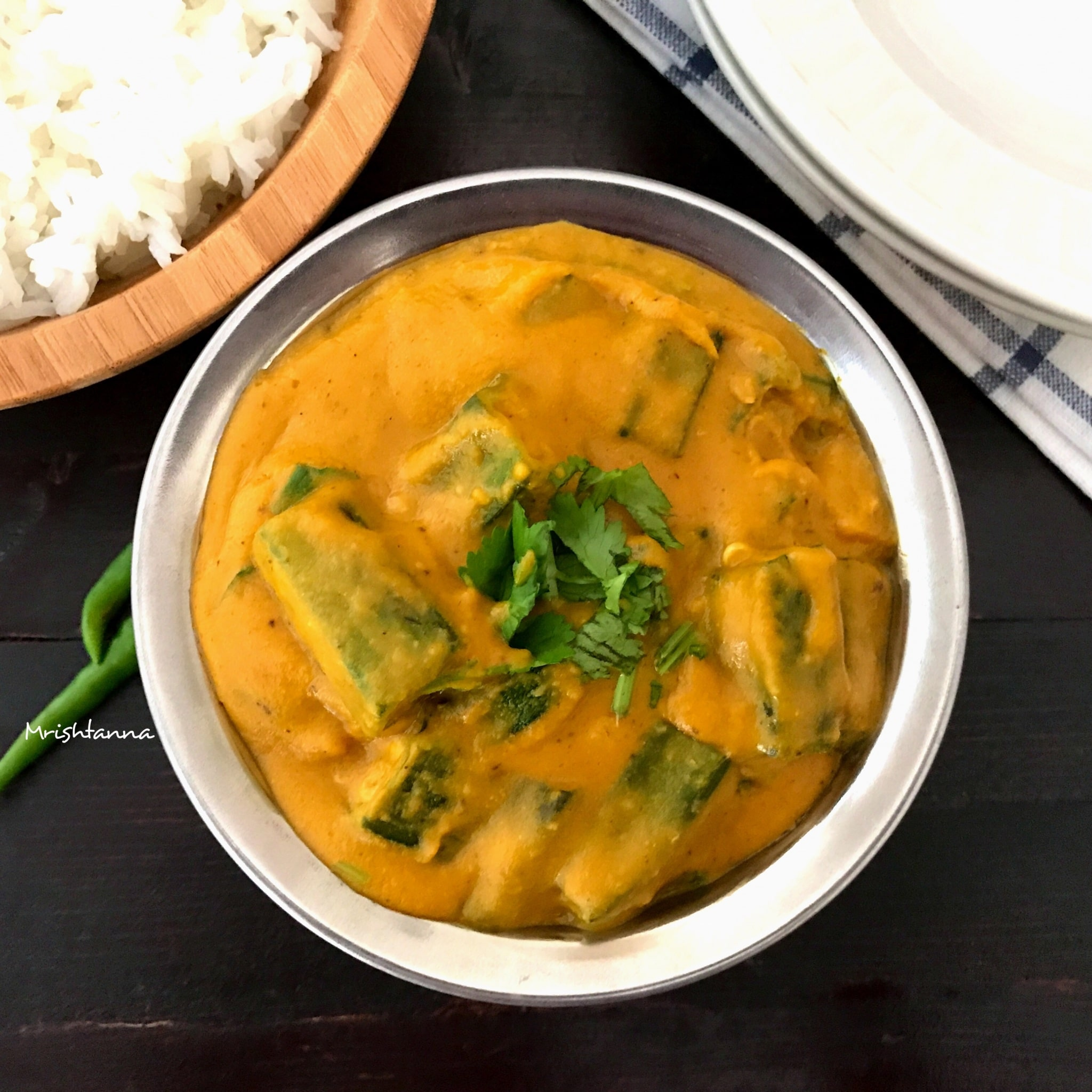 A bowl of bhindi masala is on the black table