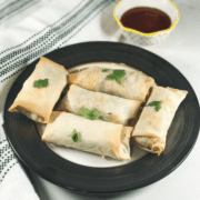 Baked Spring Rolls placed on the black plate