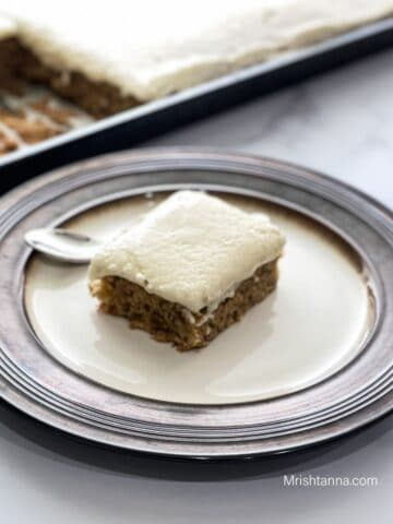 A plate is with sliced vegan banana cake and spoon on the table.