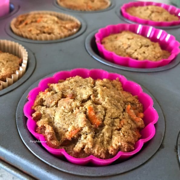 A muffin tray is filled with carrot muffins