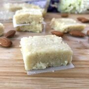 A piece of cake sitting on top of a wooden cutting board, with Almond and Barfi