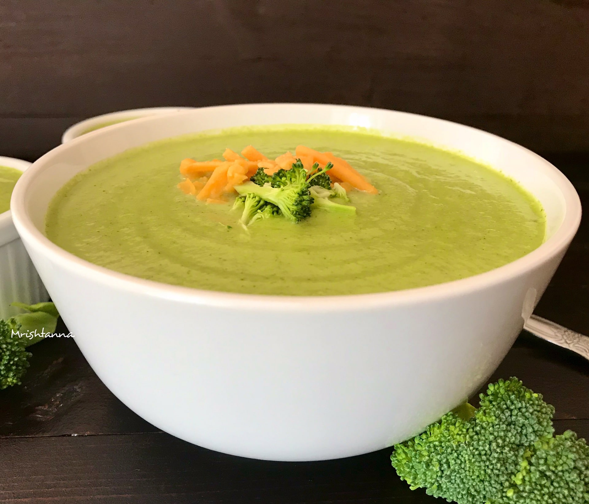 A bowl of broccoli soup and broccoli on a plate