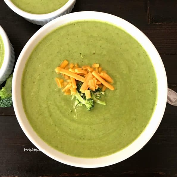 A bowl of Broccoli Soup is on the table topped with cheese