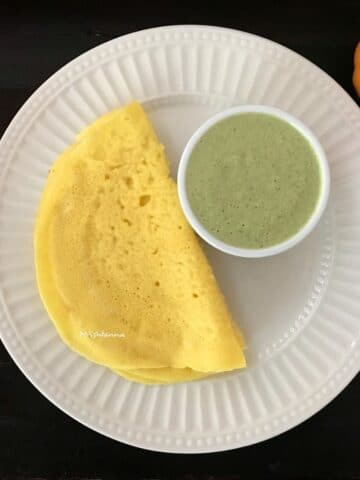 A plate is with pumpkin dosa with chutney
