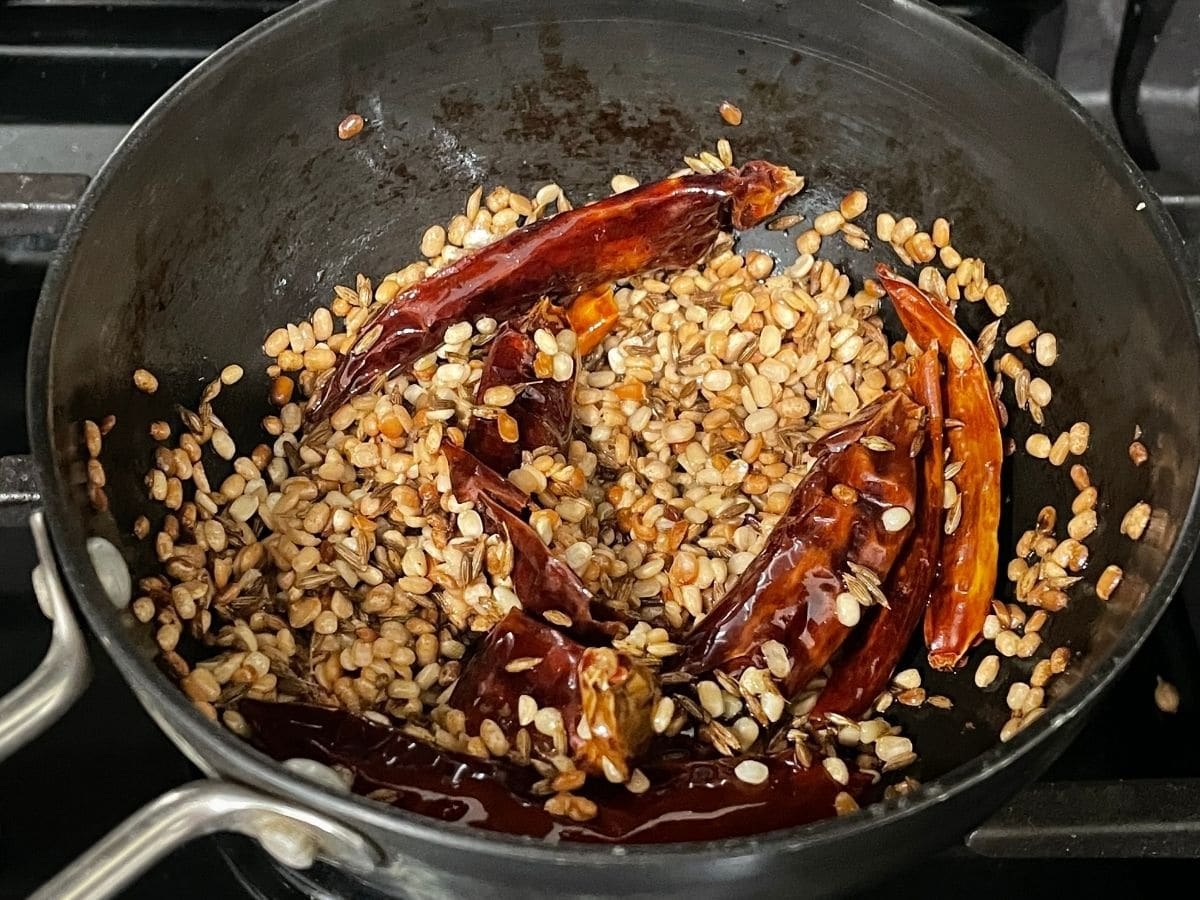 A small pan is with spices and chilies over the heat