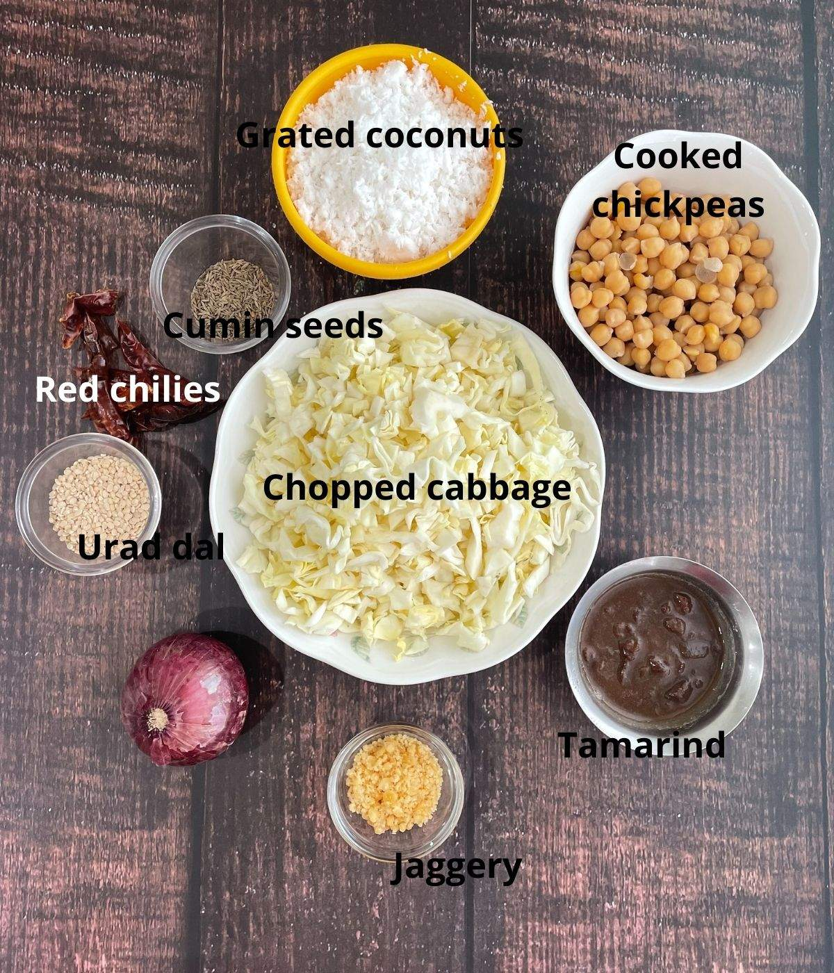 A brown surface is filled with gassi ingredients like cabbage, onion, coconuts and spices