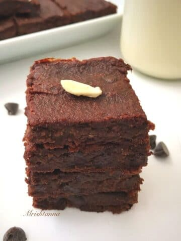 vegan brownies are stacked on the white surface along with jar of milk