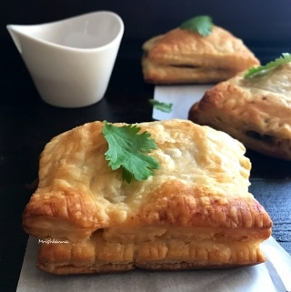A close up of a plate of food and a cup of coffee, with Puff pastry