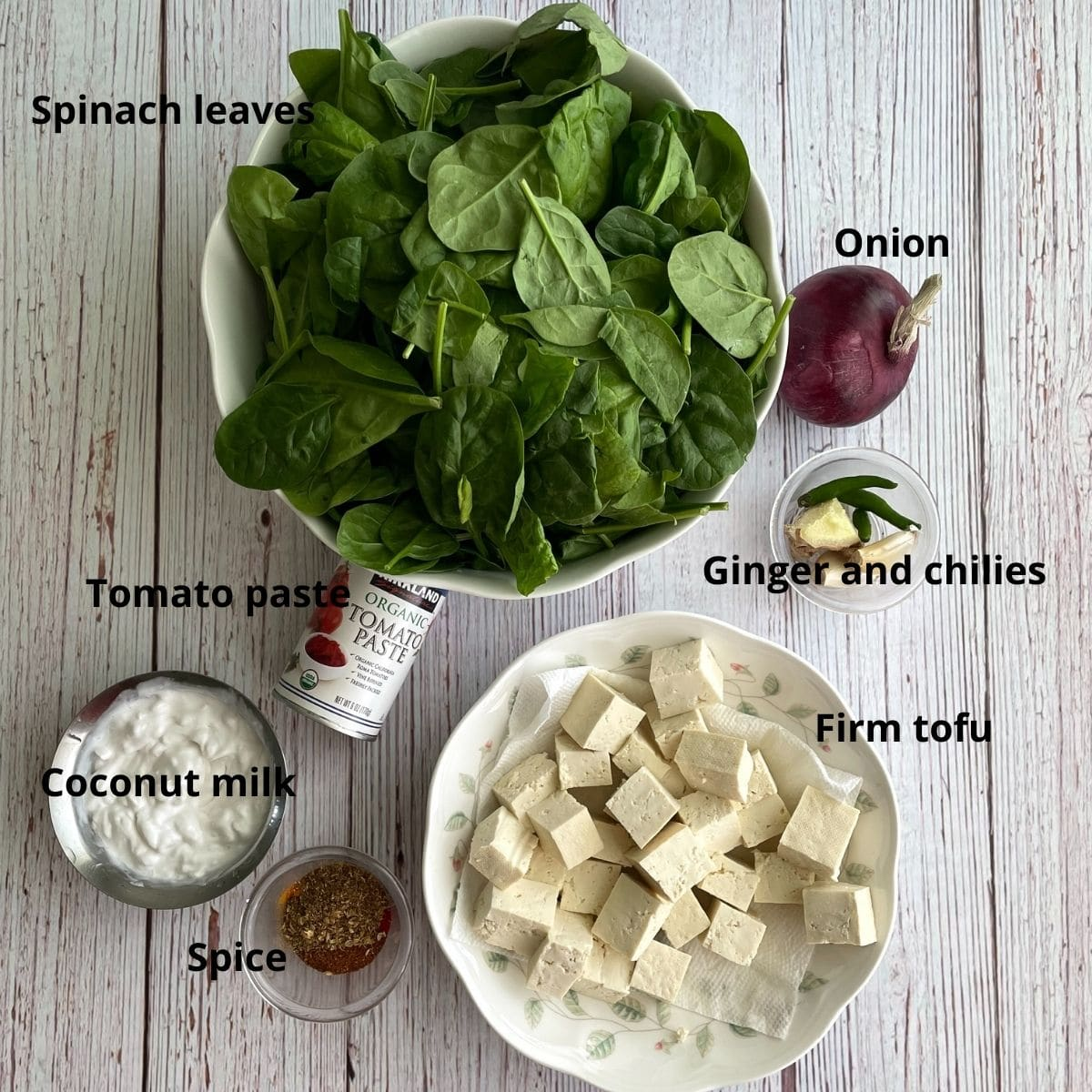 Spinach leaves, firm tofu, spices, onion and tomato paste are on the table for curry