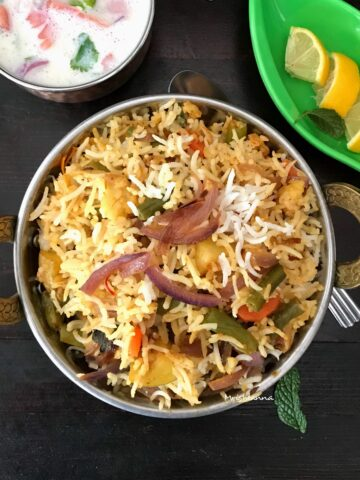 A bowl of food on a plate, with Biryani