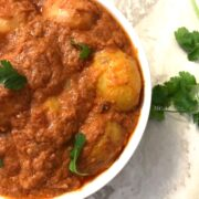 A close up of a plate of food with stew, with Dum Aloo