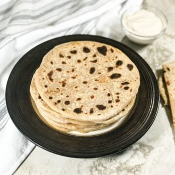 A plate of cauliflower paratha is on the table along with yogurt on the bowl