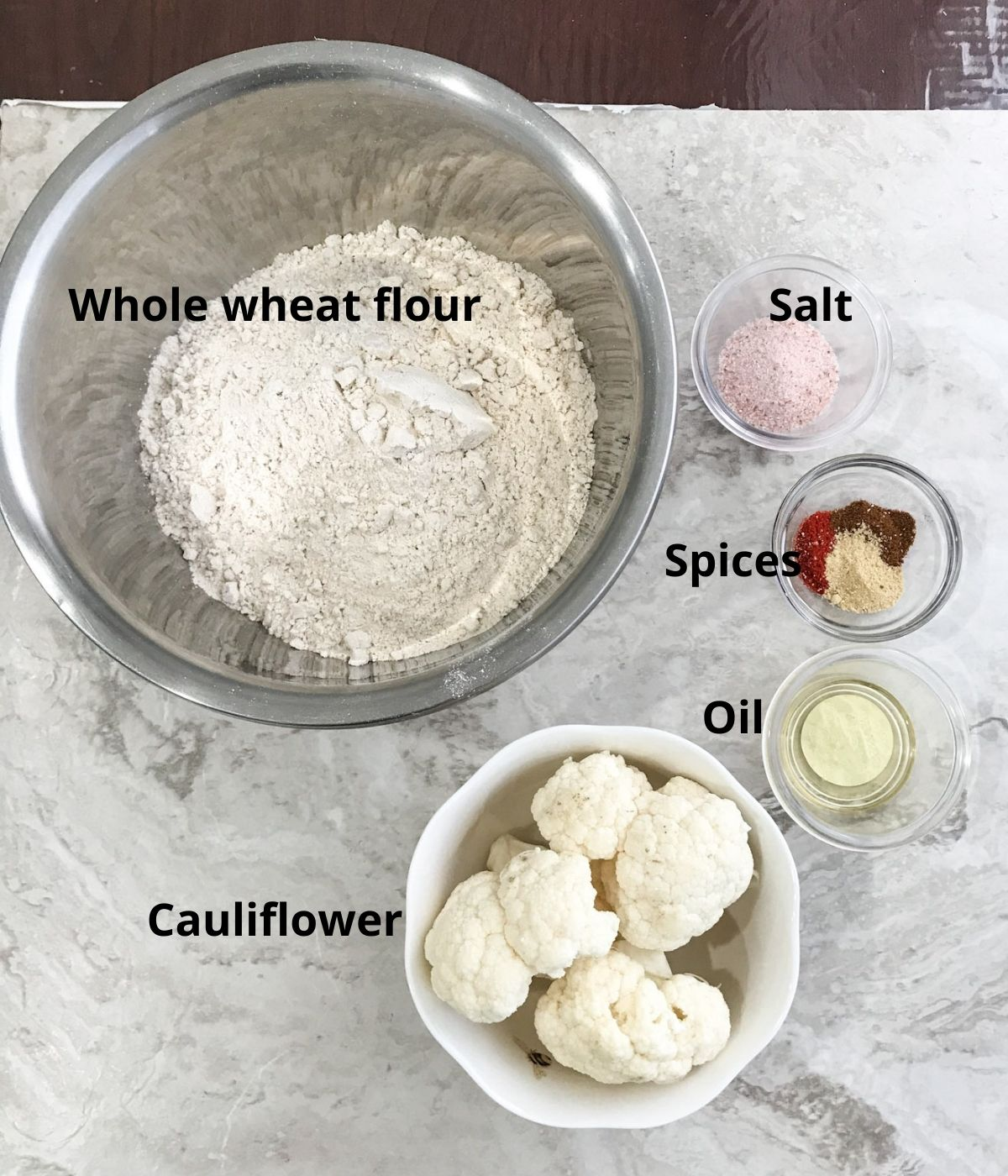 All the ingredients like flour,cauliflower and spices are placed on the flat surface for paratha
