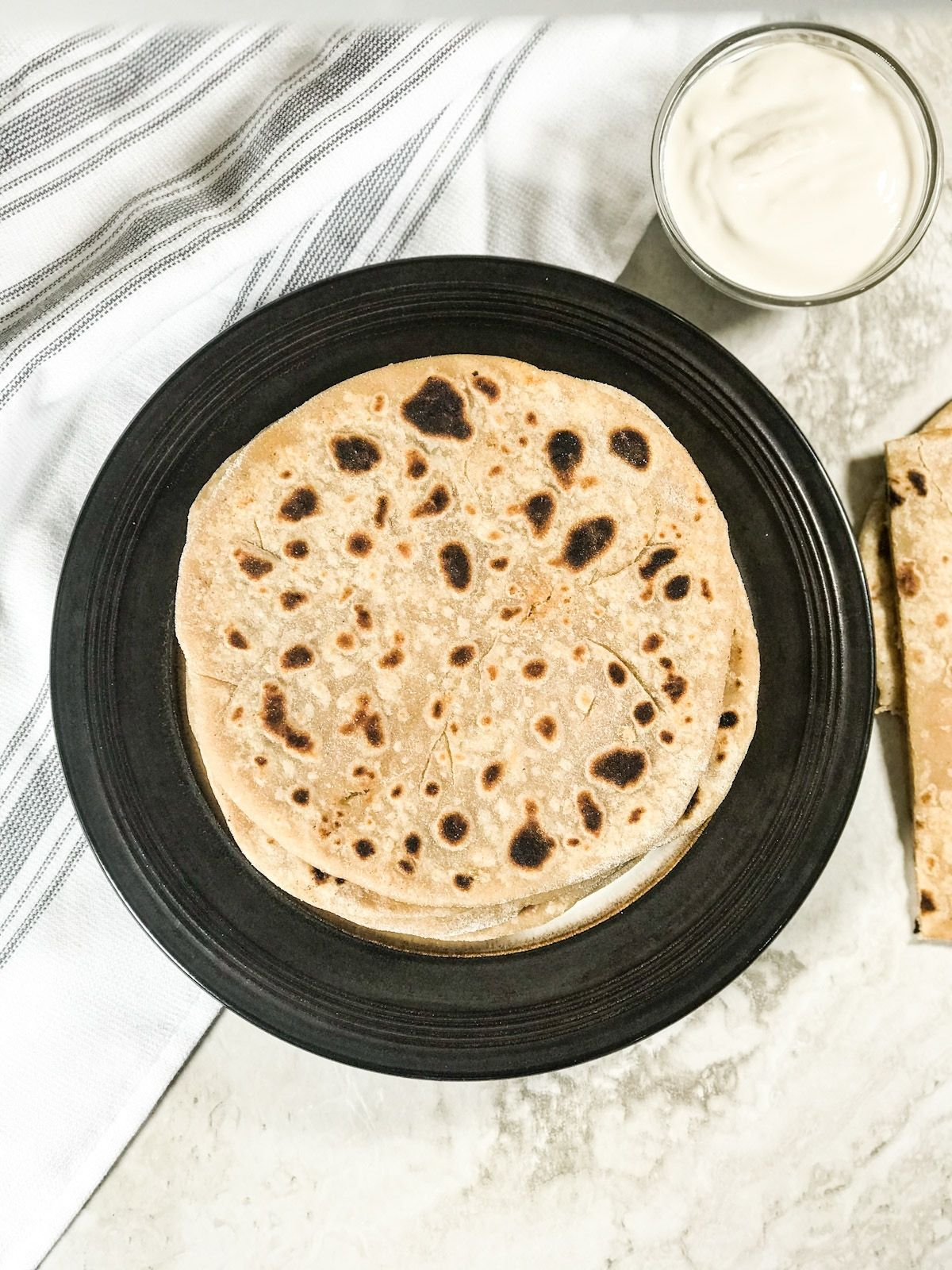 A plate of gobi paratha with side of coconut milk yogurt is on the white surface