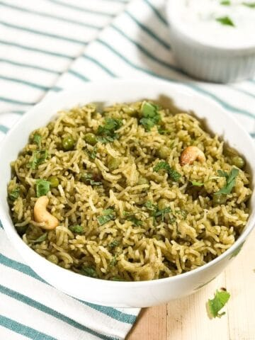 A bowl is with matar pulao and topped with cilantro