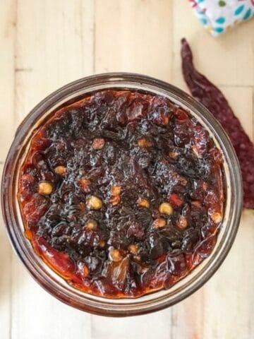A glass jar is filled with szechuan hot sauce