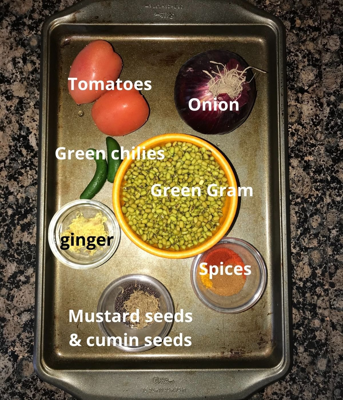 A tray is filled with dal ingredients like onion, tomatoes, green gram,spices