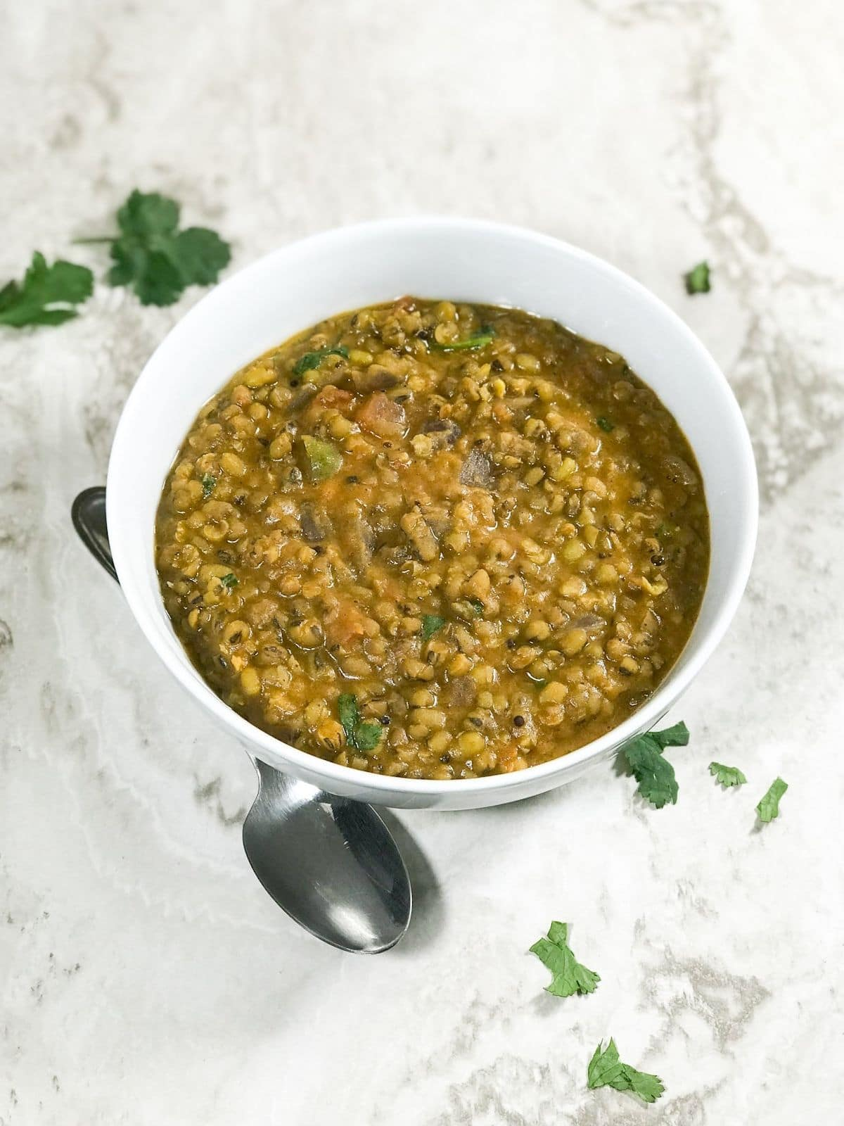 A white bowl is filled with green gram dal on the white table
