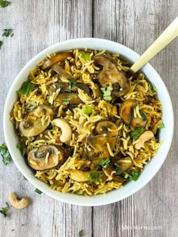 A white bowl is with mushroom rice and topped with cilantro and cashews